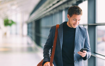 photo of young casually dressed businessman looking at his cellphone walking through airport